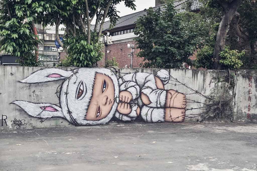 Alex Face graffiti mural with broken wall in Bangkok